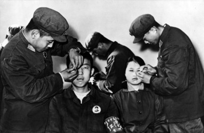 Hombres coloca aguja a adolescentes durante sesión de acupuntura