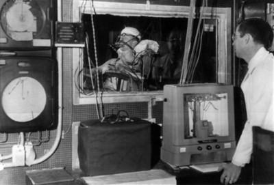 Hombre observa a persona dentro de un simulador