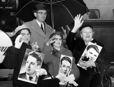 """Mujeres con fotografías de """"espías"""" saludan junto a un avión"""