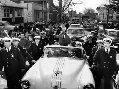 Gente observa a espías desfilar automóvil por calle de la ciudad