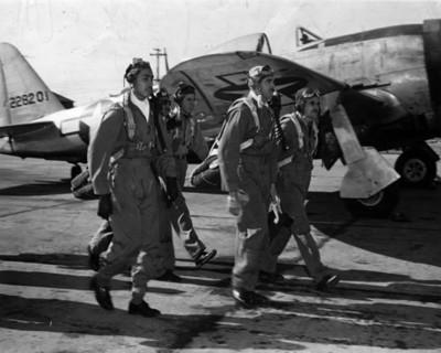Aviadores del escuadrón 201 caminan junto a avión de la armada estadounidense