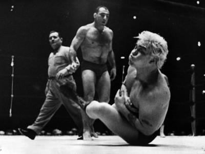 Luchador cae a la lona durante pelea deportiva