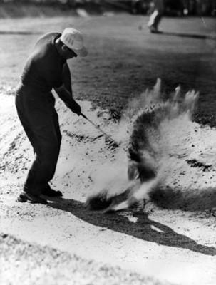 Golfista realiza tiro en una trampa de arena