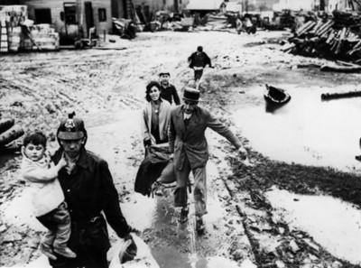 Damnificados por inundación cruzan por zona de desastre guiados ppor un bombero