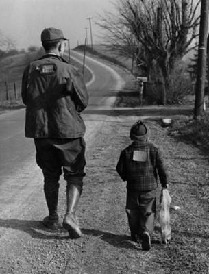 Hombre y niño cazadores caminan junto a una carretera