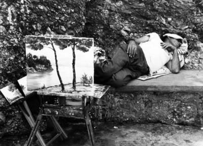 Hombre duerme en una banca junto a pintura de un paisaje