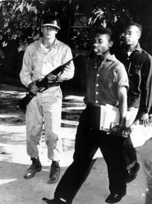 """Hombres """"negros"""" caminan frente a un soldado"""
