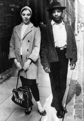 Mujer junto a hombre negro en una calle, retrato