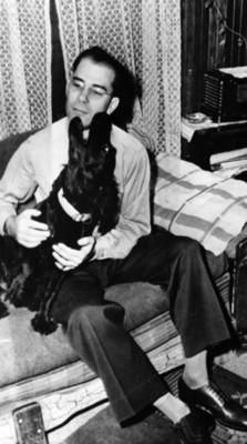 Hombre sentado en una cama abraza un perro