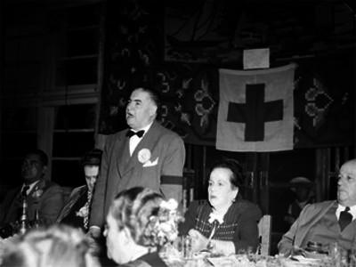 Alejandro Quijano, Licenciado acompañado de su esposa y otras personalidades hace uso de la palabra durante un banquete de la Cruz Roja