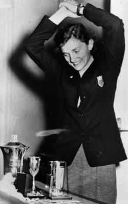 Mujer celebra junto a trofeos