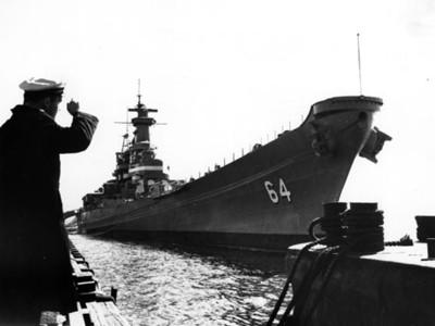Marino observa barco anclado en un puerto