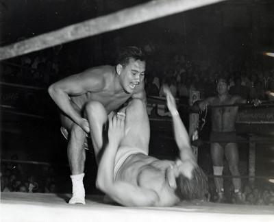 Luchador sujeta por las piernas a su rival