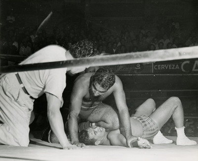 Luchadores y referee durante función