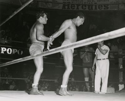 Luchador sujeta por los brazos a su rival durante una función