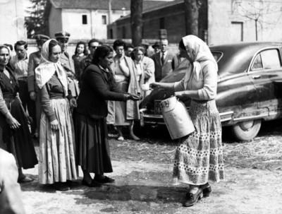 Gitana da agua a mujer para lavarse las manos en una calle