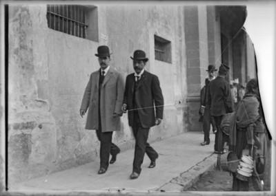 Hombres caminan por una calle, retrato