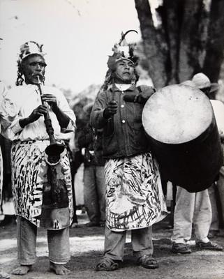Músicos indígenas tocando sus instrumentos rústicos