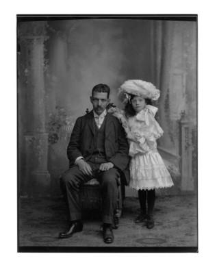 Hombre sentado junto a niña con sombrero de plumas, retrato