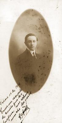 Hombre joven con anteojos y traje posa para retrato