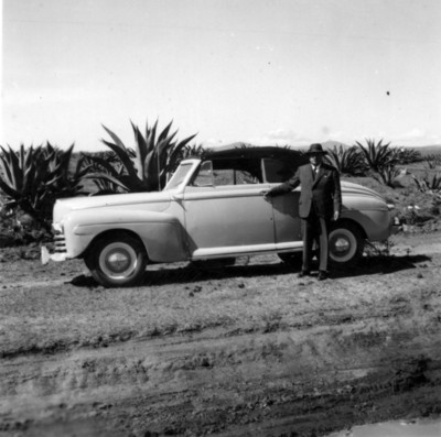 Hombre posa junto a automóvil, vista de paisaje