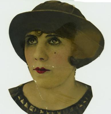 Mujer mira hacia arriba a la derecha, porta blusa y sombrero, retrato de tres cuartos