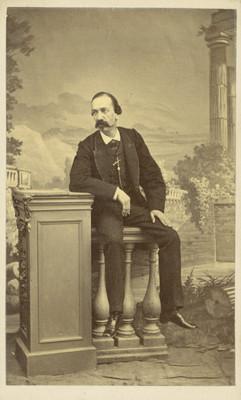 Jesús Campos Urrutia con rostro de perfil tres cuartos, sentado sobre un barandal