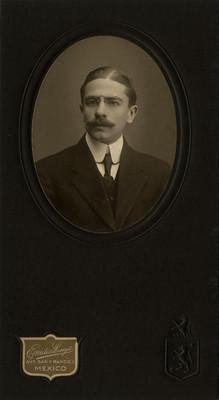 Hombre con traje mira a la cámara, retrato en óvalo con soporte secundario