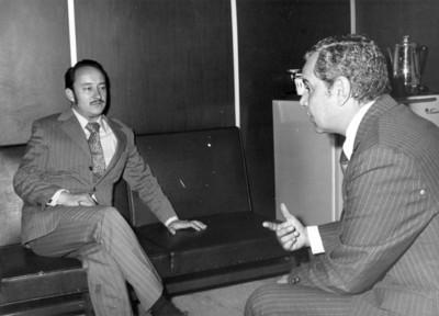 Hombres conversan durante entrevista periodística, sentados en la sala de una oficina