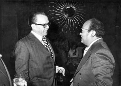 Hombres con anteojos conversan entre sí, durante reunión