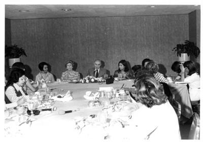 Alfonso García Robles da conferencia al centro de una mesa en reunión con mujeres