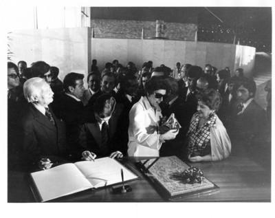 Adolfo Suárez firma el libro de visitas del museo mientras su esposa recibe una figura de cerámica