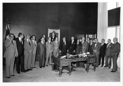 Santiago Roel de pie reunido con empresarios dentro de su oficina en la S.R.E.