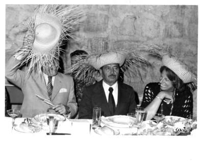 Walter Scheel levanta sombrero de palma con su mano derecha durante cena, a su lado se encuentra Eliseo Jiménez Ruíz y Mildred Wirtz de Scheel