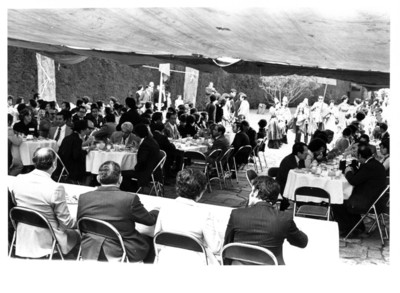 José López Portillo de espaldas, sentado al rededor de mesa durante comida de bienvenida
