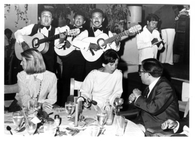 Marcelino Oreja, su esposa y la señora Gloria Rodríguez de Roel sentados a la mesa escuchan a trío musical