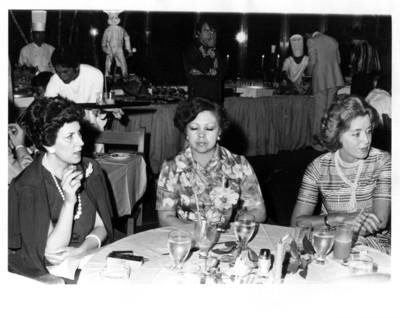 Amparo Illana Elórtegui conversa con señoras y sostiene cigarro con la mano derecha durante cena
