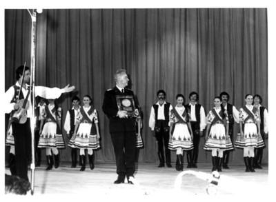 Director del grupo de danza de Hungría sostiene reconocimiento delante de bailarines, auditorio de la Secretaría de Relaciones Exteriores
