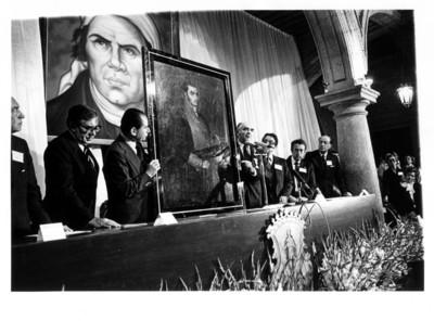 Carlos Torres Manzo y José López Portillo sostienen retrato de José María Morelos en interior del Palacio Municipal