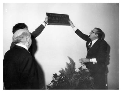 Santiago Roel García y otro hombre, colocan placa en el auditorio con el nombre de Rafael de la Colina