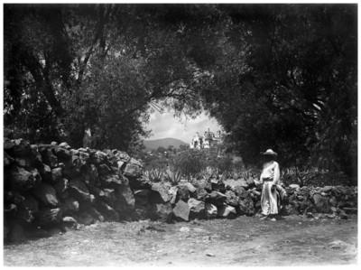 Niño junto a empedrado, al fondo la iglesia de Tepepan