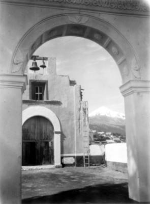 Portón y campanario de una iglesia, al fondo un volcán