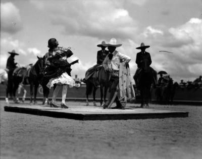 Carlos Rincón Gallardo con una mujer en un templete, bailando el jarabe tapatio