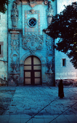 Mujer observa la fachada de arquitectura religiosa