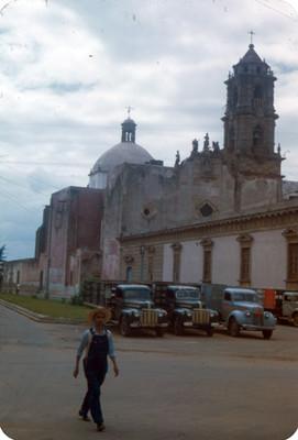 Hombre deambula en una calle, al fondo arquitectura religiosa