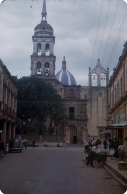 Vida cotidiana en una calle, al fondo catedral