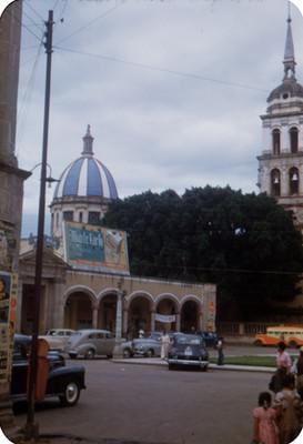 Gente deambula en una calle, al fondo catedral