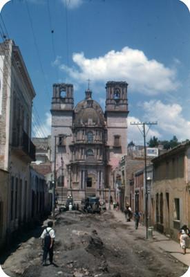 Vida cotidiana en una calle durante proceso constructivo, al fondo la Catedral