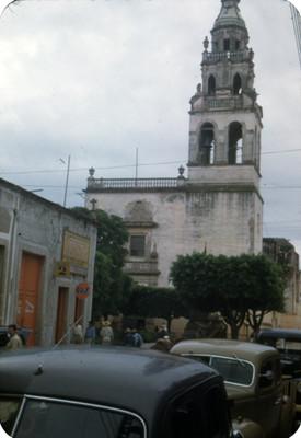Gente deambula en una calle, al fondo arquitectura religiosa