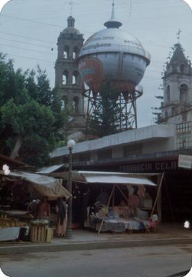Gente en un tianguis, al fondo torres del templo de San Francisco y torre hidraulica